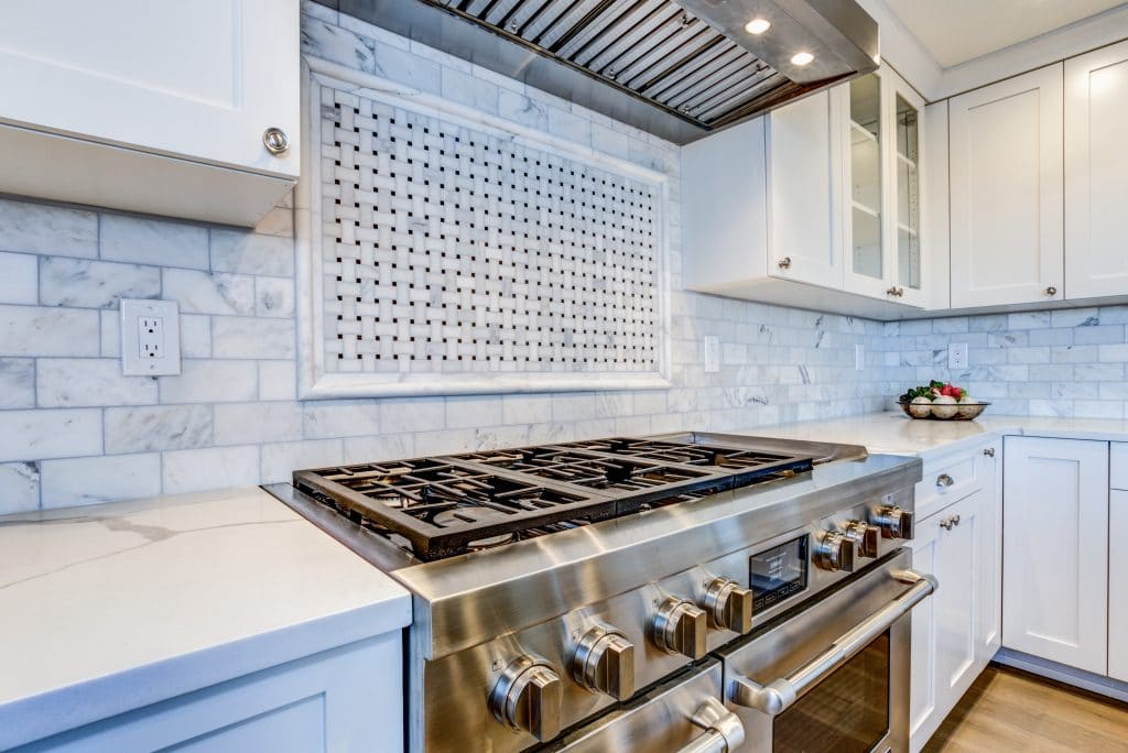 White Kitchen with stainless steel hood over gas cooktop.